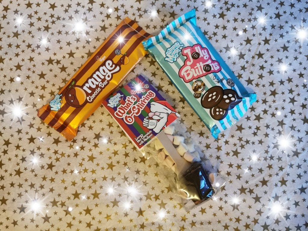 Mummy Meagz Vegan Christmas chocs, hot choc stirrer, orange choc bar and jolly buttons on a starry background