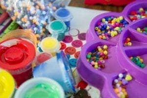 table with crafts, coloured paint pots and beads