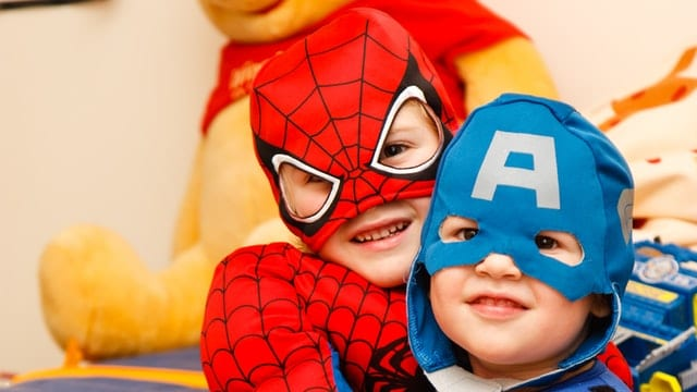 Two children dressed in costumes. One red spiderman and the other blue Captain America