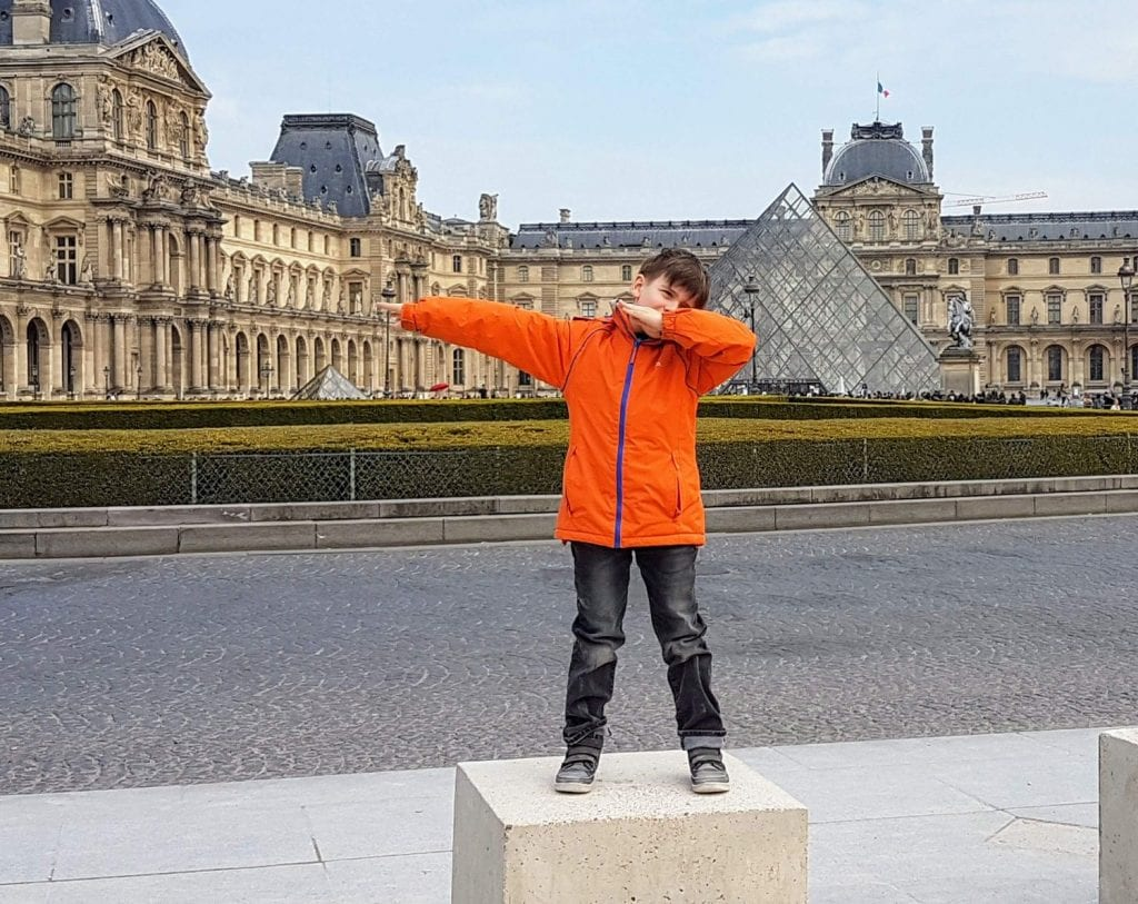 Boy in orange coat stood outside the Louvre doing a dab