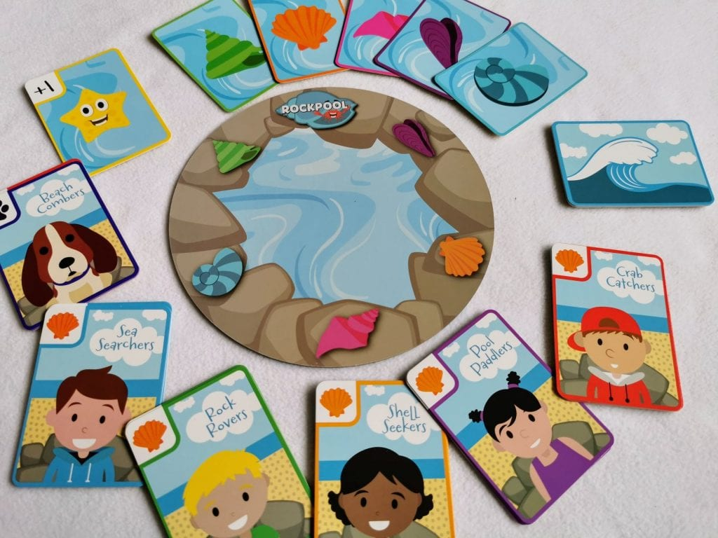 Little Gibsons Rockpool game, laid out with the rockpool board in the middle and various players cards around the outside. The cards have pictures of shells, children, dogs and rubbish on