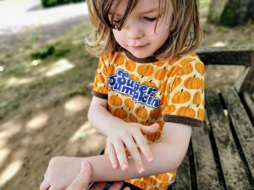 Little L, a four year old wearing an orange pumpkin t shirt, is sitting on a park bench applying a Safe + Sound plaster