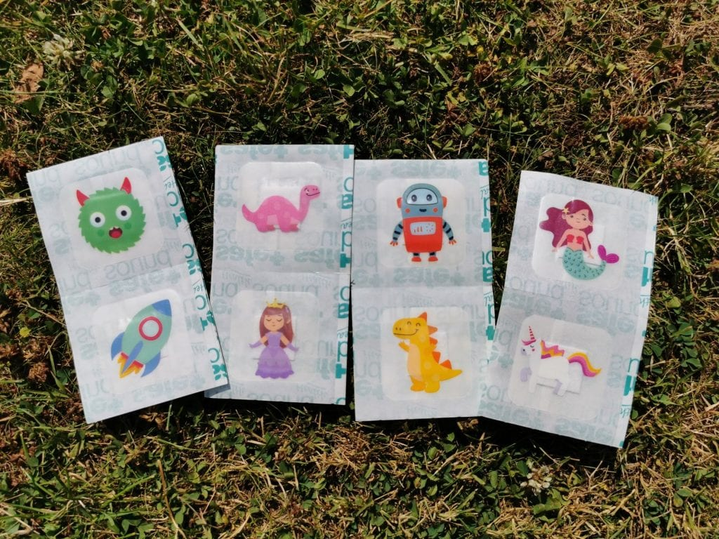 a set of 8 plasters on the grass. One each showing a green monster, blue rocket, pink dinosaur, princess in a purple dress, robot with a bue head and red legs, orange and yellow dinosaur, mermaid and a unicorn