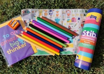 brightly coloured Stib Colouring pencils, box, stickers and card on grass