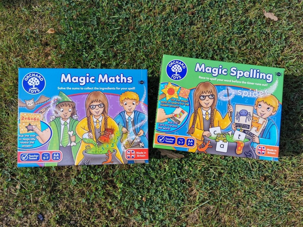 two games Magic Maths & Magic Spelling from Orchard Games displayed on grass