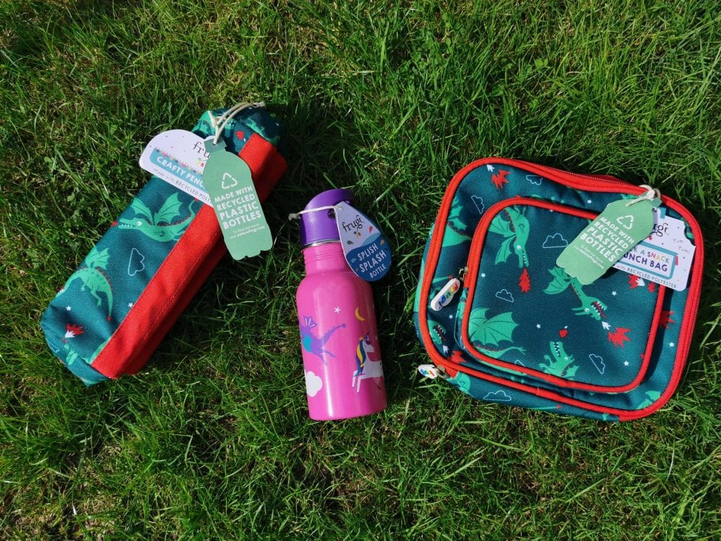 Frugi dragon print pencil case and lunch bag - dark green background with light green dragons and red flames. The stainless steel water bottle is pink with purple dragons and coloured unicorns