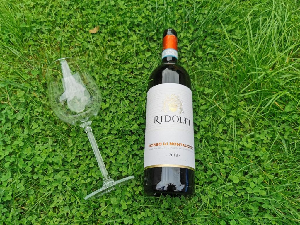 Bottle of red wine and glass lying on grass