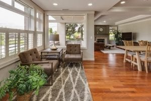 house with solid real wood flooring and a rug. Table and chairs and white walls