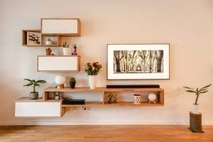 room with cream walls and wooden shelves with various plants and pictures on Real solid wood flooring