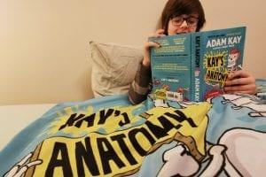 Boy, in pyjamas in bed, reading Kay's Anatomy