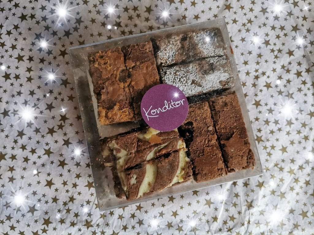 Clear plastic box of Konditor brownies. A selection of 4, on a starry background
