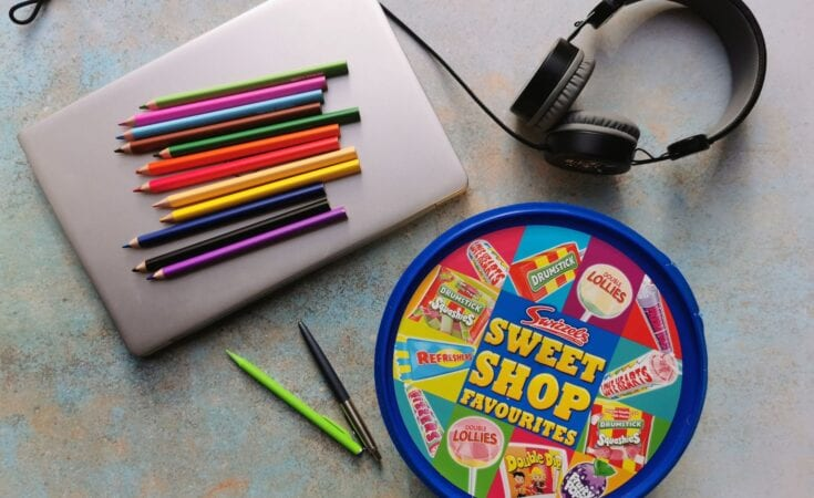 Tips & tricks for homeschooling, laptop with colouring pencils, a set of headphones and a tub of Swizzels Sweet Shop favourite