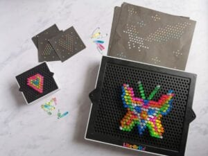 Lite Brite Mini & Lite Brite Classic toys laid side by side. Illuminated peg boards one with a colourful heart design and the other with a colourful butterfly